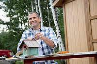 Handsome, middle_aged man repairing birdhouse