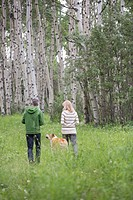 Middle-aged couple walking their dog in the woods (thumbnail)