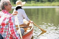 Mature couple canoeing together.