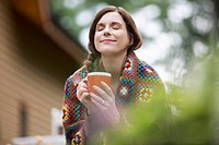 Pretty, mid_adult woman enjoying her coffee outdoors