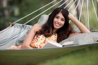 Portrait of pretty, mid_adult woman relaxing in hammock with a book