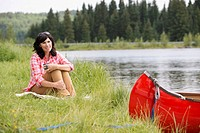 Middle-aged woman enjoying coffee outdoors by water (thumbnail)