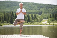 Senior man doing tree yoga pose on dock (thumbnail)