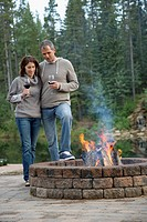 Middle_aged couple enjoying some wine by the outdoor fire