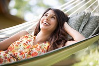 Pretty, mid_adult woman gazing up while lying in hammock