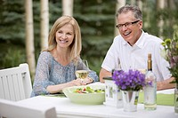 Middle_aged couple enjoying wine with their meal outdoors