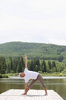Senior man doing yoga pose at the end of boat dock