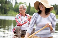Senior man paddling canoe with wife in the front