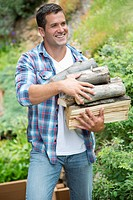 Mid-adult man carrying logs for fire building (thumbnail)
