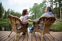 Middle_aged couple holding hands while sitting on dock