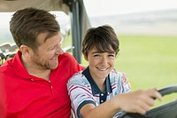 Father and son having a laugh while riding in golf cart