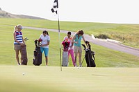 Foursome of female golfers selecting golf clubs