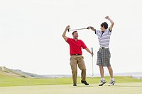 Father and son giving high_five with golf club.