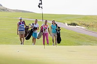 Foursome of female golfers walking towards green