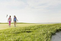 Two female golfers walking off golf green together