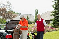 Senior and middle_aged male golfers unloading golf clubs from car