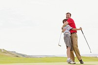 Father giving pre_teen son a bear hug on the golf course