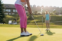 Female golfer ready to putt on golf green