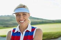 Portrait of pretty, mid_adult female golfer with visor