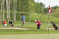 Male golfer chipping out of sand trap as fellow golfers watch