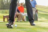 Lower half of golfer about to drive golf ball from tee.