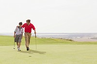 Father and pre_teen son walking together on golf green