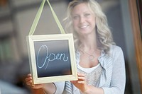Woman behind glass door showing open sign