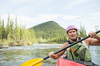 Middle-aged man kayaking on the river (thumbnail)