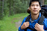 Portrait of Asian male backpacker in the woods