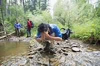 Male hiker washing his face in a stream