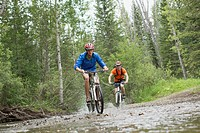 Two male mountain bikers riding through stream.