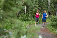 Couple running on trail through the woods