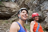 Two female rock climbers standing by rock face