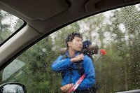View of male hiker through car window