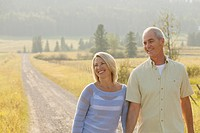 Attractive couple walking together down country road