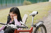 Middle_aged Asian woman taking a break from mountain biking