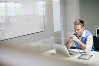 Young adult male using laptop in office (thumbnail)
