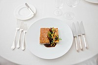 Close up of elegant place setting with meal in restaurant