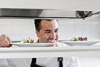 Smiling male chef preparing meal in kitchen