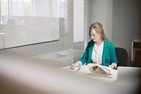 Female office worker at desk making notes