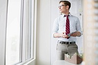Young professional with pc tablet looking out office window