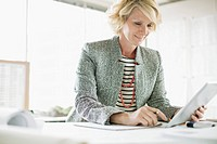 MIddle_aged businesswoman using pc tablet in modern office