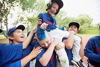 Boys baseball team giving teammate a shoulder ride.
