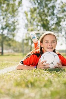 Young female soccer player lying on grass with chin on soccerball