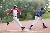 Young baseball player running for first base