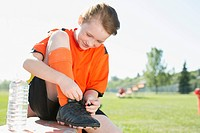 Young female soccer player tying up laces