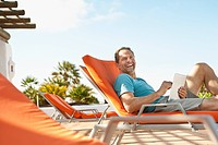 Man relaxing on sunlounger with tablet pc