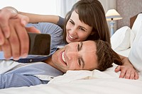 Couple lying on bed and photographing themselves with cell phone