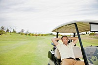 Man resting in golf cart on golf course