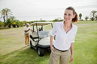Smiling woman on golf course with man standing near golf cart in background